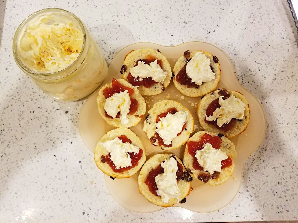 Scones with strawberry jam and home-made clotted cream, ready to eat. These scones are served